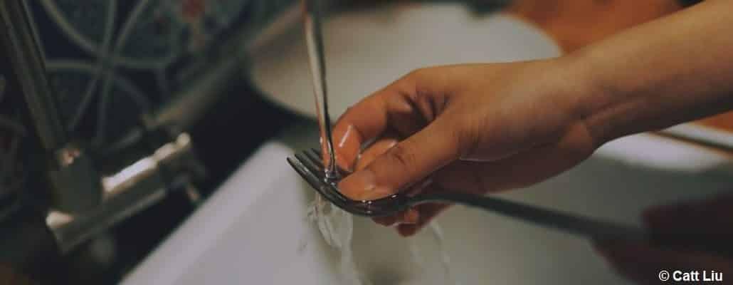 Une main qui nettoie une fourchette, tout faisant couler l'eau de l'évier