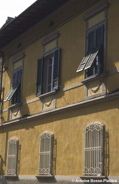 Maison jaune avec des volets et persiennes contre le soleil