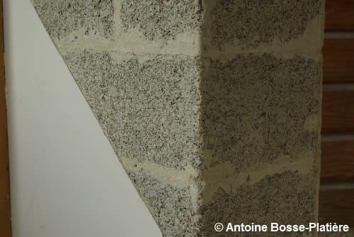 Gros plan sur un mur en blocs de chanvre maçonnés