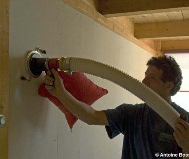 Un maçon qui isole un mur, à l'aide d'une machine qui insuffle de la ouate de cellulose