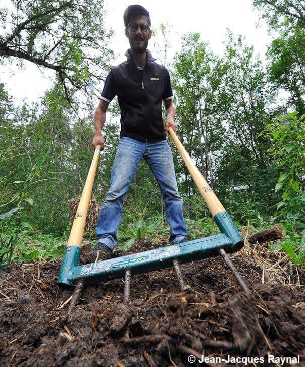 Le jardinier greline avec une fourche à bêcher