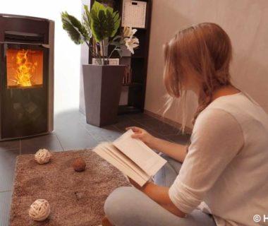 Une jeune femme assise par terre, entrain de lire un livre, devant un poêle à granulés en fonctionnement