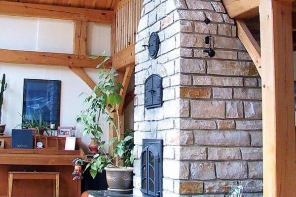 Poêle de masse artisanal en pierres qui monte jusqu'au plafond