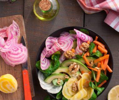 Assiette composée contenant mâche, betterave, carottes, avocats, et noix
