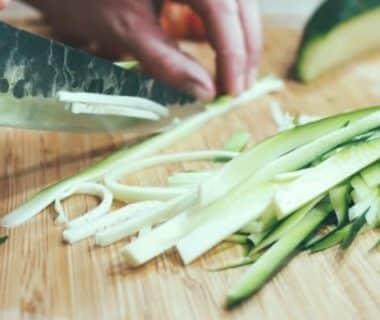 Courgette entrain d'être coupée au couteau en lamelles