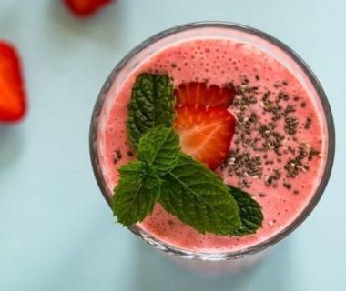 Vue en plongée sur un dessert glacé aux fruits rouges mixés, avec une fraise coupée et de la menthe en décoration