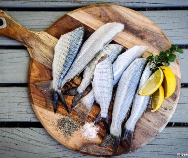 Planche avec plusieurs poissons entiers disposés et du citron