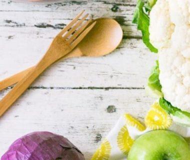 Vue en plongée sur du chou, de la pomme, une cuillère et une fourchette