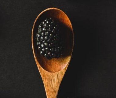 Vue en plongée sur une cuillère en bois (sur fond noir) avec une mûre posée dessus