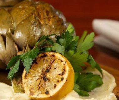 Un artichaut cuit avec un citron sur une planche en bois