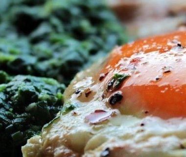 Gros plan sur un œuf au plat et des épinards
