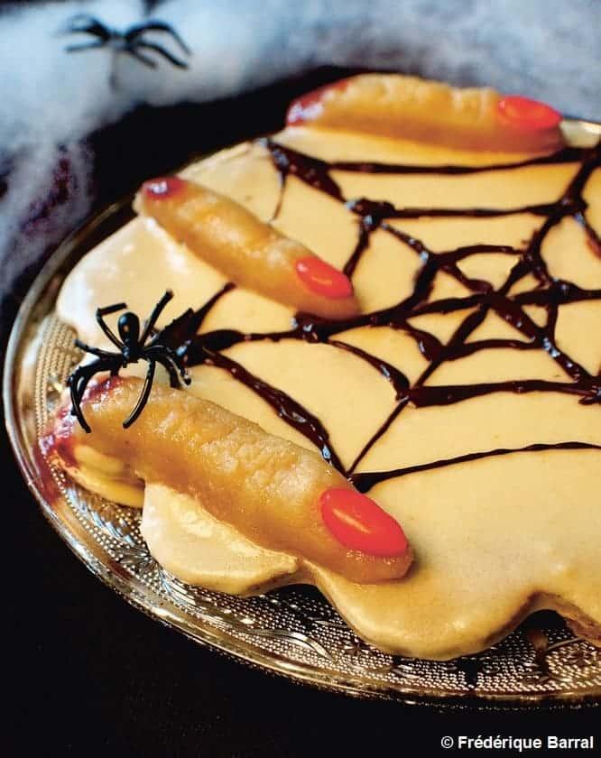 Un flan à la citrouille avec un glaçage au chocolat en forme de toile d'araignée avec des doigts découpés