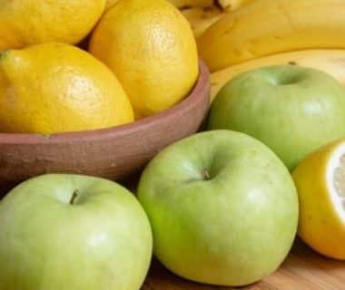 Pommes et citrons sur une planche en bois et dans un saladier