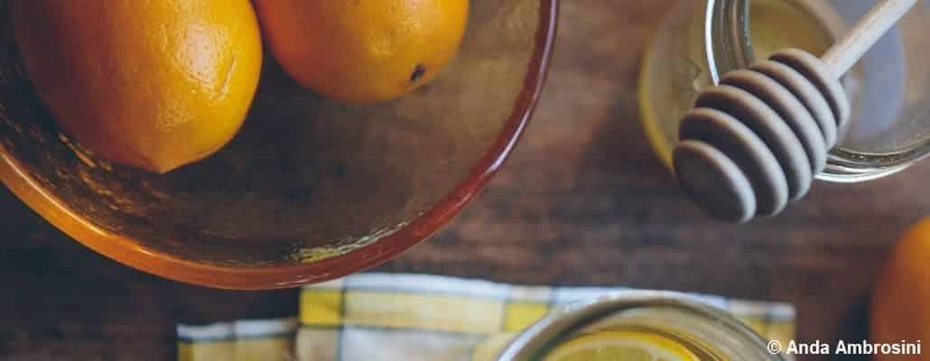 Vue en plongée d'oranges dans un saladier et d'une cuillère à miel