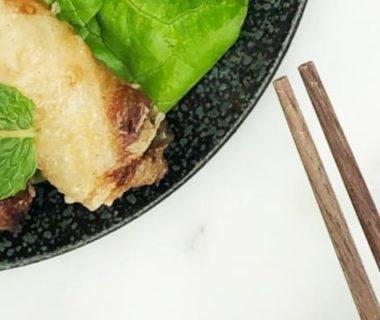 Nems dans une poêle et des baguettes japonaises