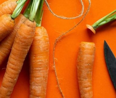 Quelques carottes et un couteau sur fond orange